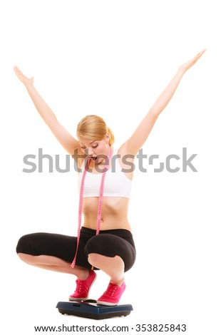 Disappointed sad young woman girl with tape measure on weighing scale can't lose weight and throw hands up in despair. Slimming dieting and healthy lifestyle concept. Isolated on white background. - stock photo