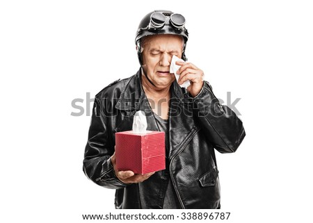 Disappointed senior biker in a black leather jacket holding a box of wipes and crying isolated on white background - stock photo