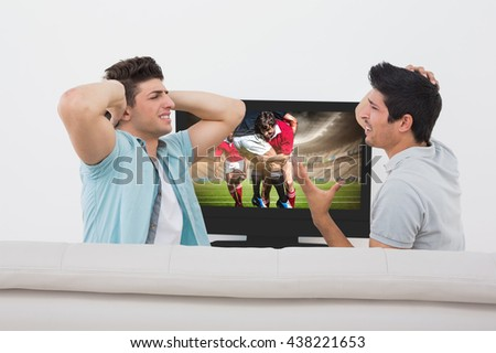 Disappointed soccer fans watching tv against rugby players tackling during game - stock photo