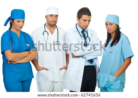 Disappointed team of different doctors standing in a row and looking down or at camera isolated on white background - stock photo