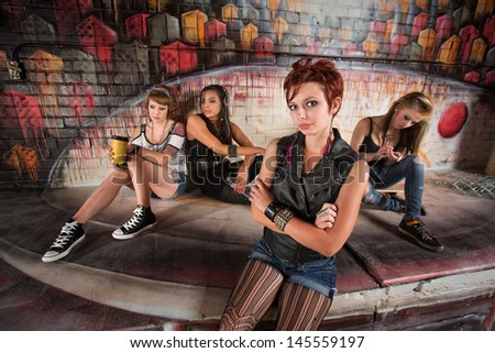 Disappointed teenager with indifferent friends behind her - stock photo