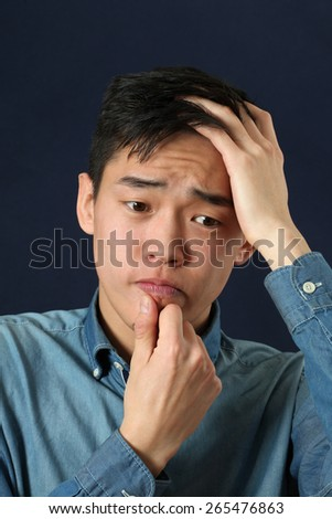 Disappointed young Asian man looking sideways - stock photo