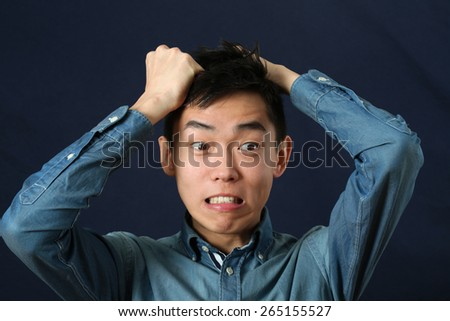 Disappointed young Asian man making face and looking sideways - stock photo