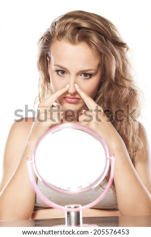 disappointed young blonde touching her nose in the mirror - stock photo