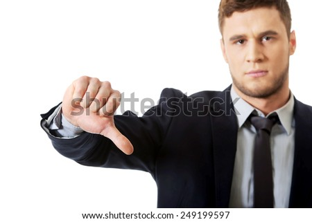 Disappointed young business man with thumb down. - stock photo