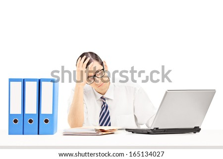 Disappointed young businessman at his workplace isolated on white background - stock photo
