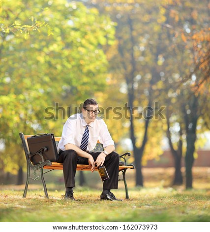 Disappointed young businessman sitting on a wooden bench with bottle in his hand, in park, shot with tilt and shift - stock photo