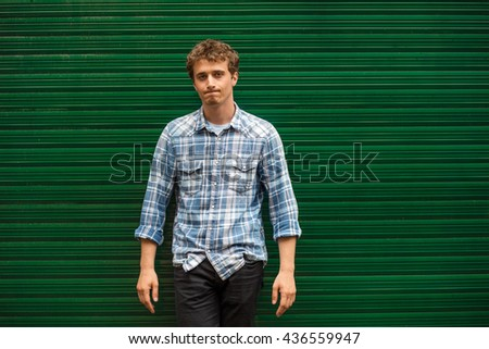 disappointed young man casual dressed standing against green background,  with arms folded - stock photo