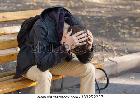 Disappointed young man sitting on a wooden bench in the park and holding his head with his hands - stock photo