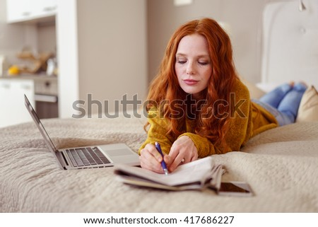 Disappointed young redhead woman lying on her bed marking off a newspaper advertisement as she answers the classifieds - stock photo