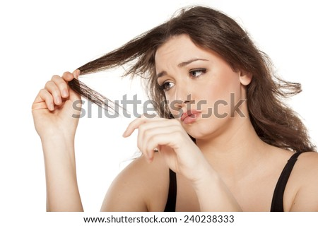 disappointed young woman looks at the tops of her hair - stock photo