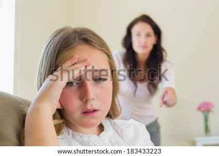 Disappointment girl with mother scolding her in background at home - stock photo