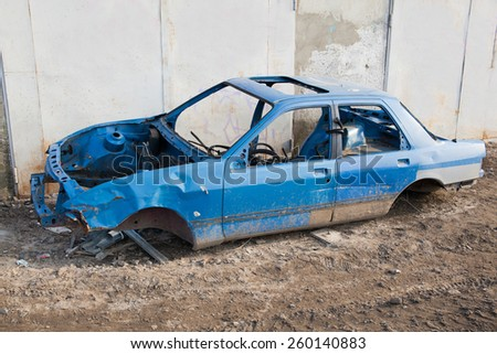 Disassembled car body standing near the garage gate - stock photo
