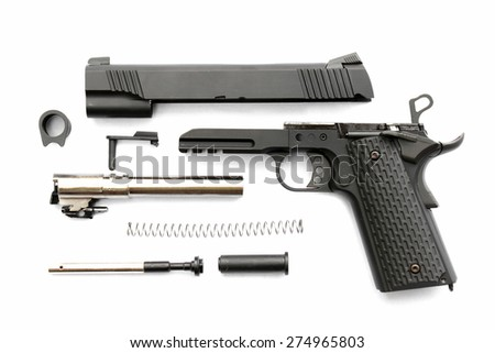 Disassembled handgun on white background. Seperate parts handgun. Pistol Part. - stock photo