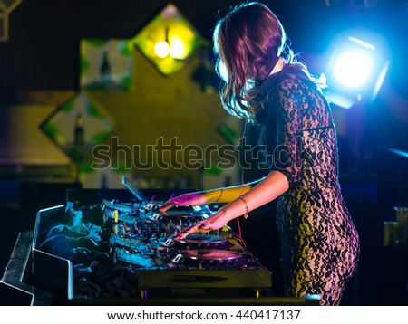 Disc jockey brunette girl mixing electronic music in club - stock photo