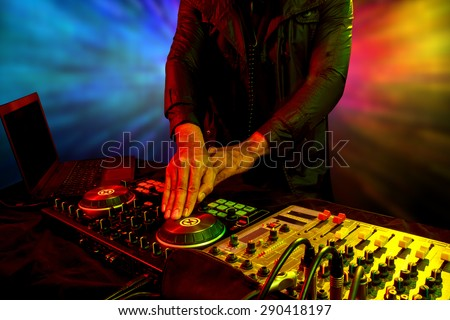 Disc jockey mixes turntable with dance song in nightclub at party - stock photo