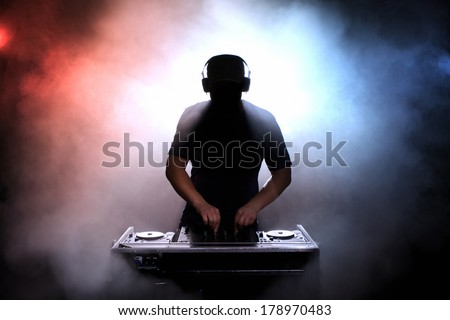 Disc jokey, DJ, silhouette over foggy illuminated background - stock photo