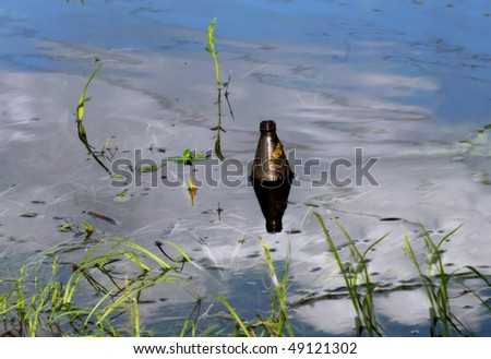 Discarded beer bottle floats in a stagnant pool of water in a ditch.  Bottle is half submerged and sits in the reflection from an overhead cloud and blue sky. - stock photo