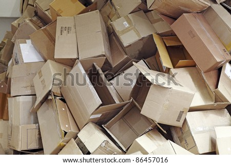 Discarded brown colored corrugated paper carton boxes piled up for recycle process. - stock photo