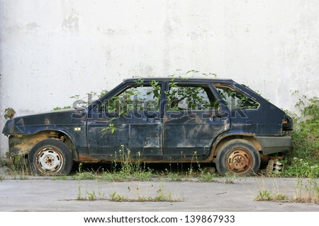discarded old car in overgrown grass next to the wall - stock photo