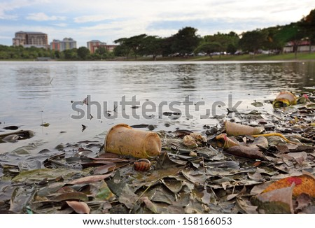 Discarded plastic debris polluting a waterway in an urban park.  - stock photo