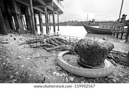 Discarded rubber tire polluting a rural coastal village.  - stock photo