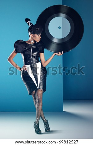 Disco african women stands with big vinyl record in her hand - stock photo