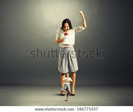 discontented businesswoman screaming at small yoga woman over dark background - stock photo