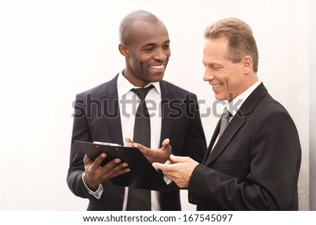 Discussing a new project. Two cheerful business men looking at the note pad and gesturing - stock photo
