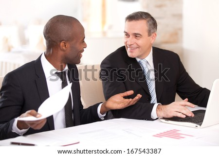 Discussing a project. Two cheerful business people in formalwear discussing something while one of them gesturing and smiling - stock photo