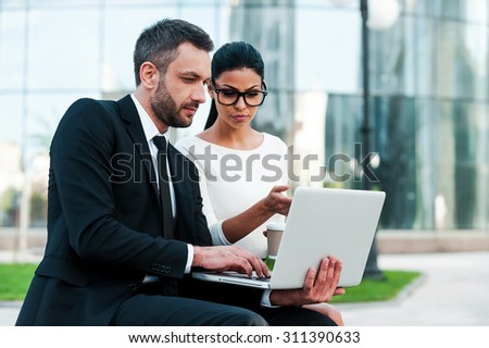 Discussing business project together. Two confident young business people working on laptop while sitting outdoors - stock photo