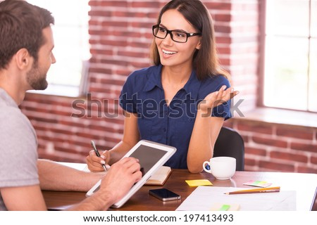 Discussing business. Two cheerful business people in casual wear talking and gesturing while sitting at the table  - stock photo