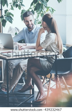 Discussing business. Two young business people in smart casual wear discussing something while sitting at the office desk together  - stock photo