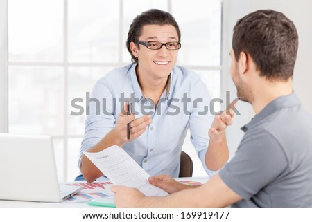 Discussing contract. Two cheerful business people in casual wear discussing something and gesturing while sitting at the table - stock photo