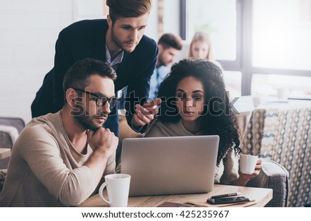 Discussing new project together. Thoughtful business people looking at laptop and discussing something - stock photo