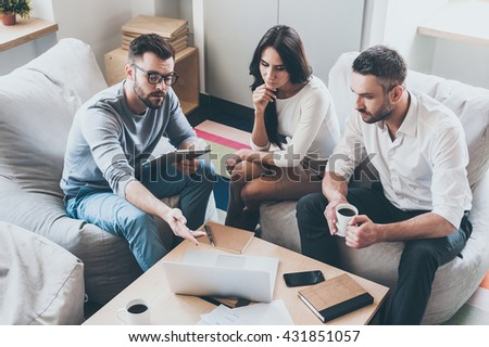Discussing new project together. Top view of confident young man pointing laptop while sitting together with his colleagues in office  - stock photo