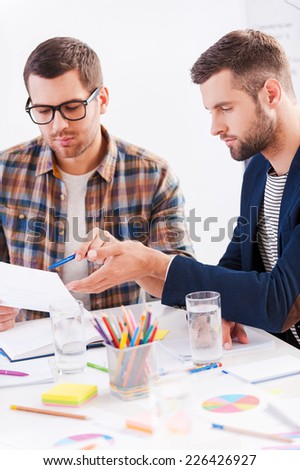 Discussing new project. Two confident business people in smart casual wear sitting together at the table and discussing something - stock photo