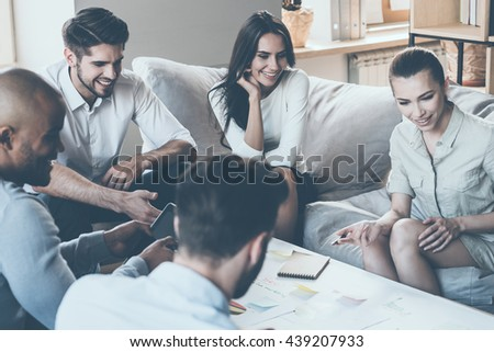 Discussing new strategy. Group of young business people discussing something and smiling while sitting together and looking at paper laying on desk  - stock photo
