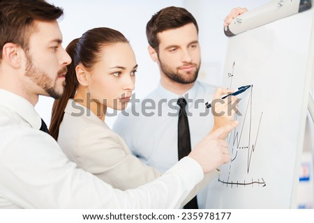 Discussing progress graph. Three confident business people discussing graph on the whiteboard while standing close to each other  - stock photo