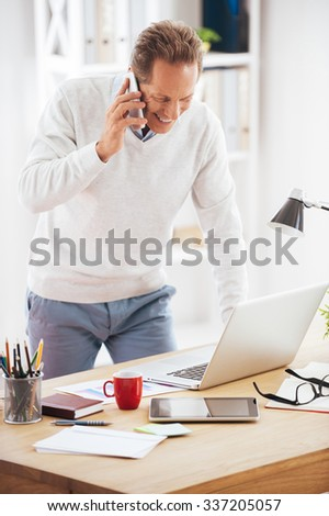 Discussing some business issues. Cheerful mature man talking on the mobile phone and looking at his laptop while standing near his desk in office - stock photo