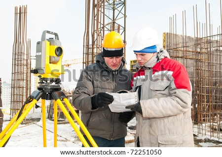 Discussing Surveyor worker and assistant at construction site in winter with theodolite equipment - stock photo