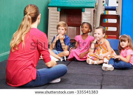 Discussion group of children in kindergarten talking to nursery teacher - stock photo