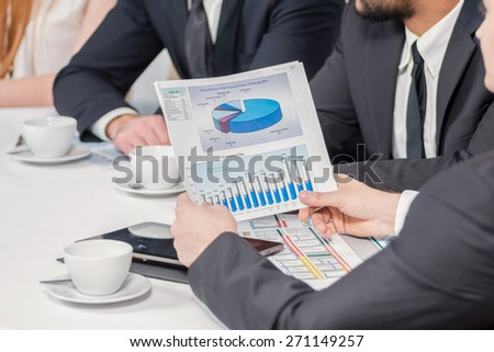 Discussions of the financial statements. Four confident successful businessmen at a meeting while sitting at a table discussing business doing in the office - stock photo