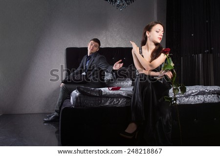 Disdainful attractive young woman sitting on the bed dressed in elegant black evening wear ignoring her husband or boyfriend as he pleads with her to forgive him or overlook an indiscretion - stock photo