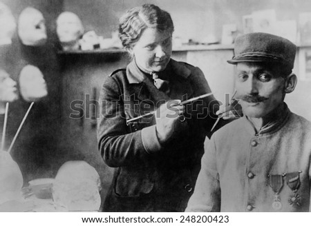 Disfigured WW1 Veteran's mask gets finishing touches by sculptor Anna Ladd. 1918. The French soldier's mask of sculpted and painted copper was made by American artist in July 1918. - stock photo