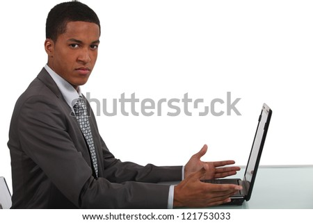 Disgruntled office worker sat with laptop - stock photo