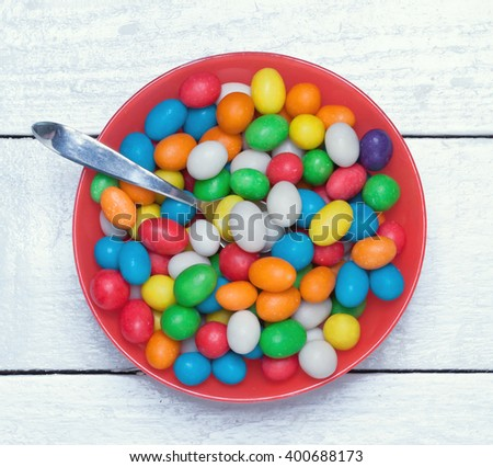 dish filled with colorful candy on a wooden surface.closeup.view from above.toned  - stock photo