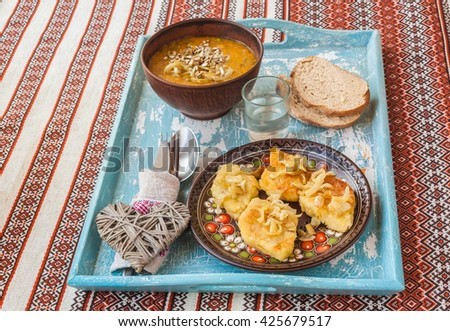 Dish Lithuanian, Polish, Belarusian cuisine rhombuses potato with fried onions  and pumpkin soup on the tray - stock photo