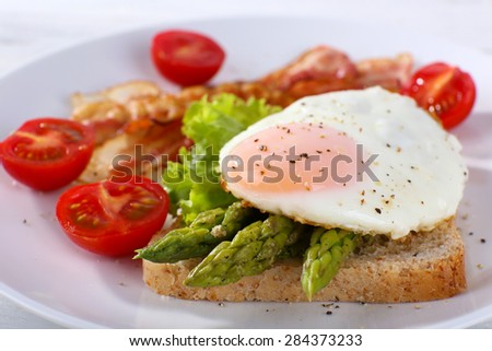 Dish of asparagus and egg in plate on table, closeup - stock photo