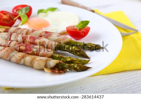 Dish of asparagus with bacon and egg in plate on table, closeup - stock photo